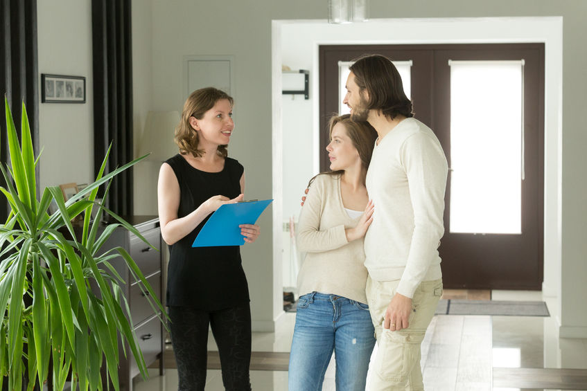 Leasing Agent talking to young couple, prospective tenants, in the foyer of an apartment building