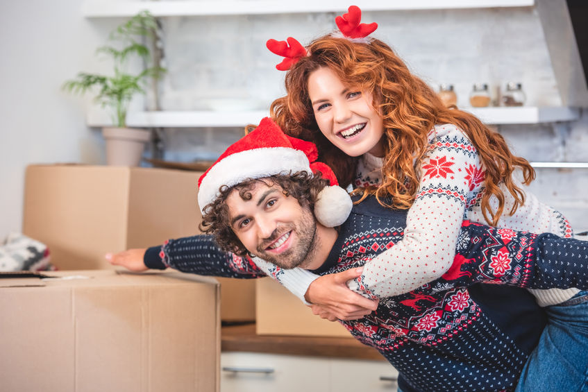 Happy young couple piggybacking and smiling at camera while moving during the winter holidays