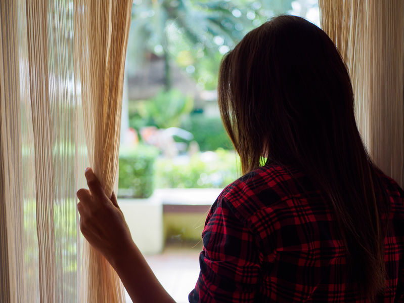 Rear view of a young woman holding the curtains open to look out of a large window in her apartment
